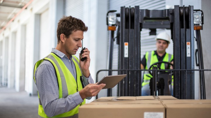 Operations manager working alongside fork lift driver