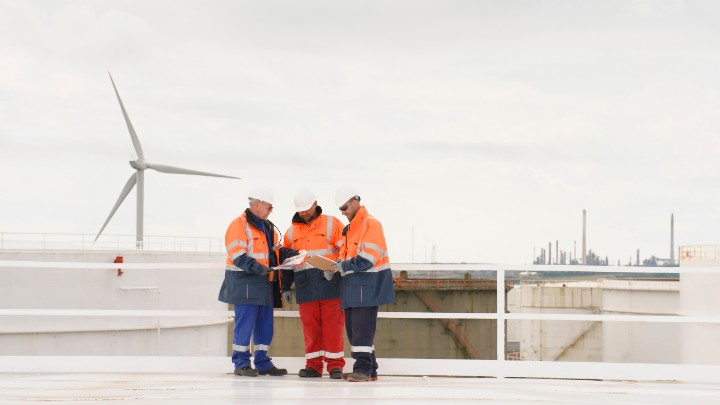Factory operations team outside with wind turbine in background